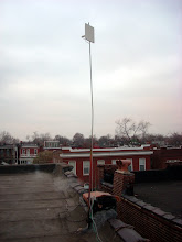 """Photo: 10foot mast with Ubiquiti Bullet2HP access point with 15.5dB panel antenna.  The mast is constructed from 0.5"""" electrical conduit inserted into an old mount for a TV antenna."""