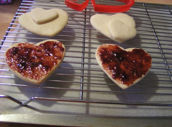 DECORATING COOKIES  Spread raspberry preserves on the back side of 2 large cookies.