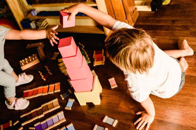 Enfants qui jouent avec la tour rose montessori et plaquettes de couleurs montessori