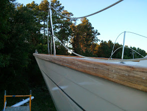 Photo: Sanding down the portside bow.  Along the full length of the cap rails we drilled out and filled all fastener holes.