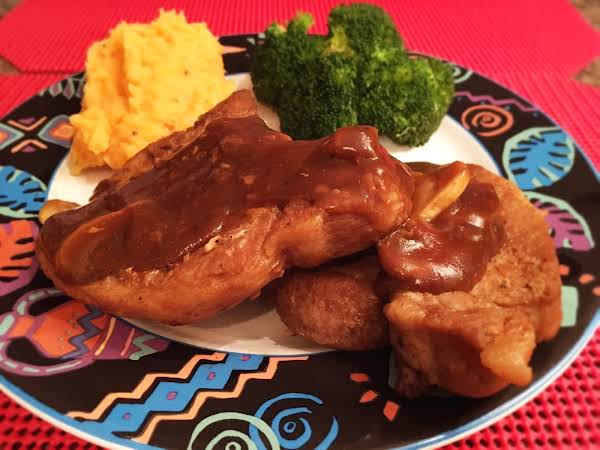 Two Pork Chops On A Plate With Mashed Potatoes And Broccoli Florets, And Topped With A Sauce.