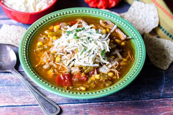 Turkey Tortilla Soup With Shredded Cheese On Top.