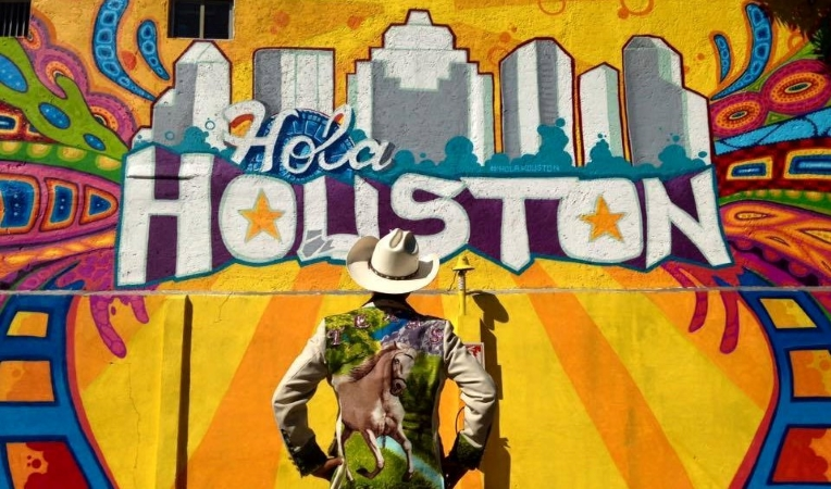 a cowboy standing in front of a mural in Houston, Texas