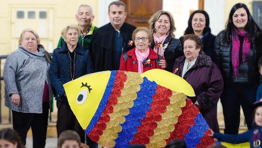 Los participantes en los talleres de envejecimiento con una de las sardinas elaboradas.