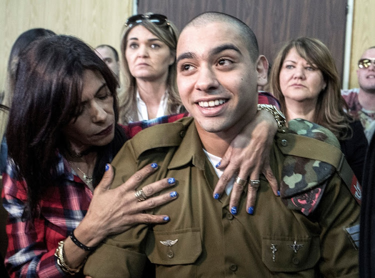 Israeli soldier Elor Azaria's mother embraces him at his sentencing in Tel Aviv, Israel, on Tuesday.  Picture: REUTERS/JIM HOLLANDER