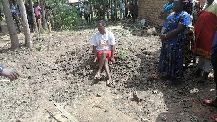Abenny Jachiga's widow Belinda Aluoch siting on the grave. /Faith Matete