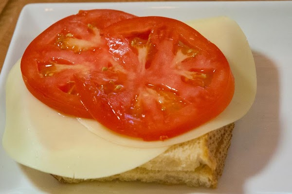 Place the toasted bread on a plate, and add the provolone cheese, and tomato.