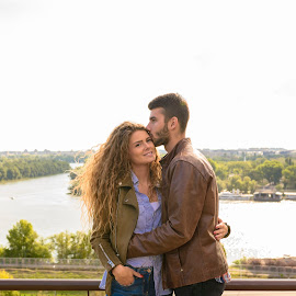 Young couple with the sweetest emotions by Vera Arsic - People Couples ( young women, romance, two people, friendship, heterosexual couple, city life, togetherness, young adult, river bank, kissing, embracing, model, hugging, smiling, attractive, lovers, lifestyles, girlfriend, enjoyment, color image, adult, photography, handsome, city, 20-29 years, boyfriend, casual clothing, affectionate, modern, romantic, happiness, joy, dating, flirting, caucasian ethnicity, nature, carefree, sexy, intimate, young men, people, love emotion, standing, young couple, outdoors, bonding, couple relationship, feelings, fun, fashion )