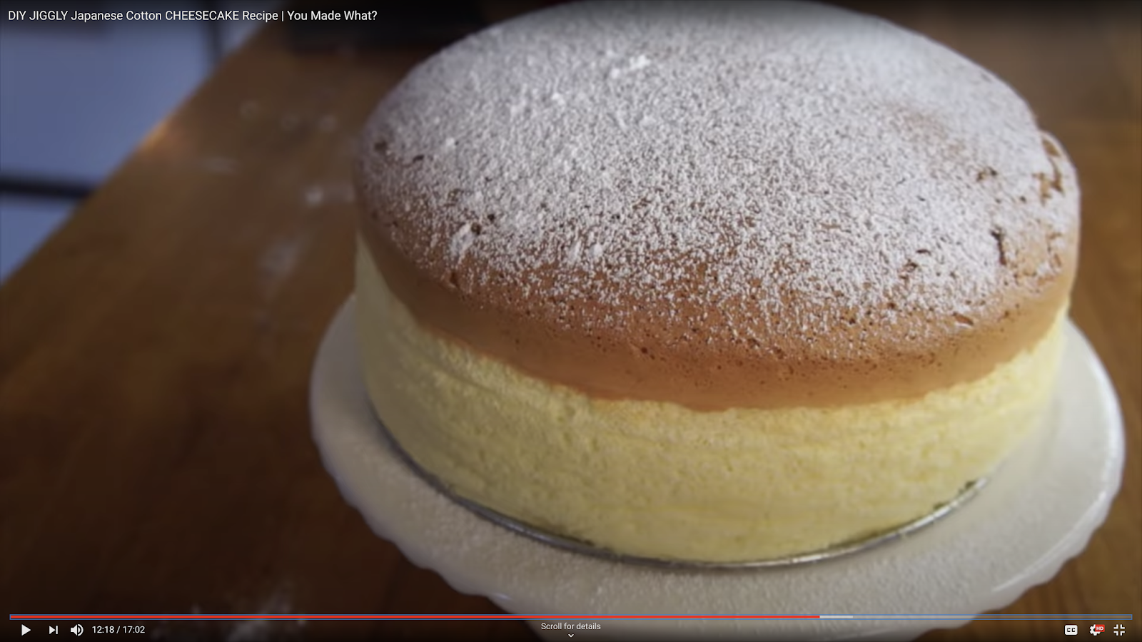 A golden brown puffy Japanese cheesecake dusted with powdered sugar on a cake stand.