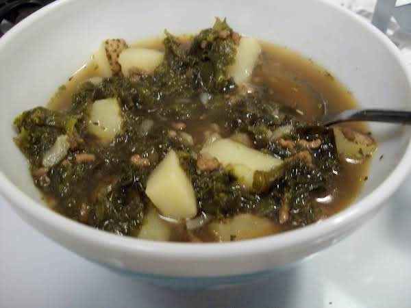 A Bowl Of Kale, Ground Beef And Potatoes In An Onion Soup Base.