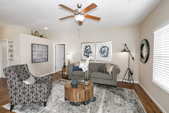 Staged living room including white trim, neutral walls, wood-inspired floors, ceiling fan with light, window with blind