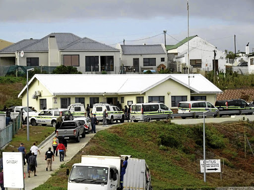 Police and Hawks vehicles at the Department of Agriculture, Forestry and Fisheries building in Gansbaai.