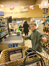 Photo: Mommy's helper loading the groceries onto the conveyor belt.