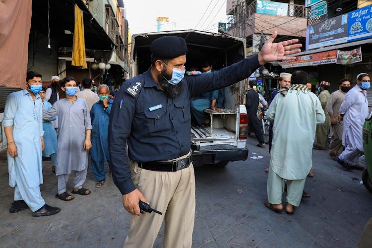 一名警察于4月25日,在2021年4月25日,巴基斯坦的Peshawar在Peshawars的安全方案遵循Coronavirus安全方案,因为Covid-19的传播继续。