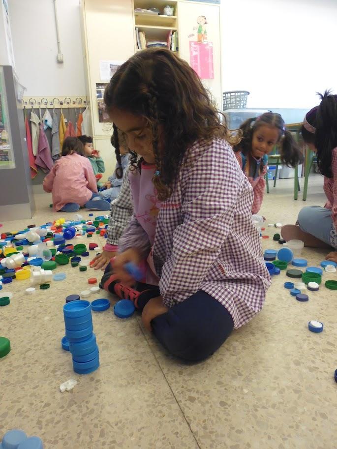 Alumna observant l'equilibri apilant taps de la mateixa mida i color.