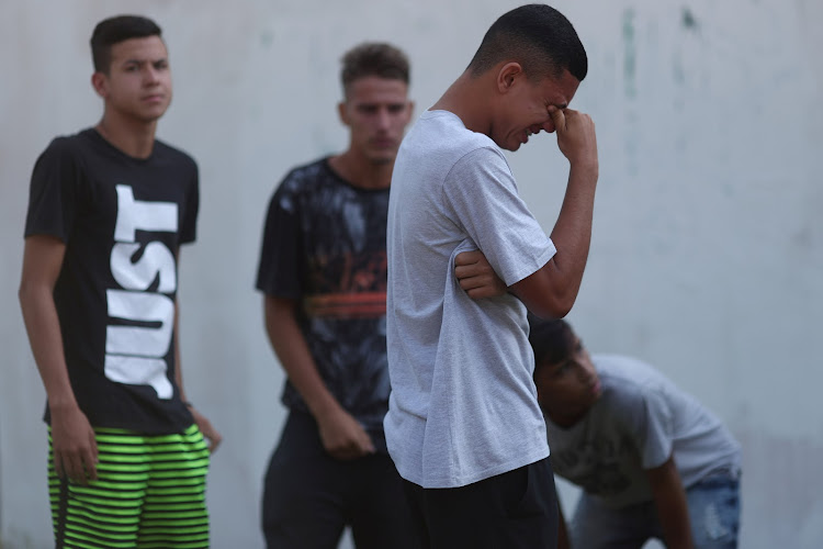 People wait for information in front of the training centre of Rio's soccer club Flamengo, after a deadly fire in Rio de Janeiro, Brazil, on February 8 2019.