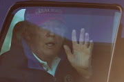 US president Donald Trump waves to supporters as he drives past Freedom Plaza as he returns to the White House after playing golf in Washington, US, on November 14 2020.