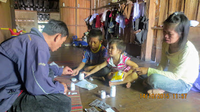 Photo: Healthcare volunteer, Chaliao, distributing medicine to Pitoon and mum.