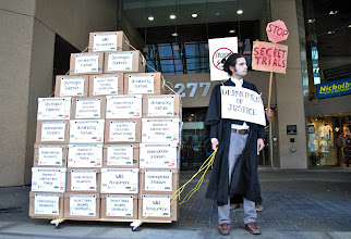 Photo: A supporter of Mohammad Mahjoub stands in front of the Toronto offices of the Canadian Security and Intelligence Services (CSIS) with a stack of boxes symbolizing documents belonging to Mahjoub and his defense that were stolen, viewed, and copied by the Department of Justice in the summer of 2010.