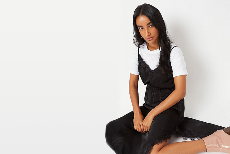 Woman sitting on the floor wearing a white T-shirt with a black eyelash lace trim midi slip dress on top