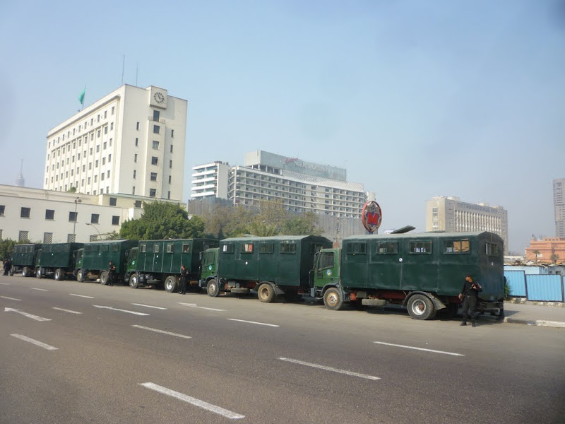 Photo: Trucks jammed full of riot police officers lined one side of Tahrir square, preparing for 3:00 p.m. - the time set for protest kick-off.  Friday prayers would finish at 1:30 or 2:00pm - Muslim men are required in the Qur'an to attend Friday prayers.