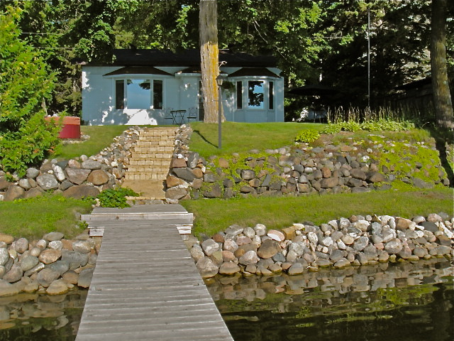 Photo: View looking back at the cabin from the end of the dock.  NIce grassy area to place your beach towels, lawn chairs, or beach blanket while you swim.