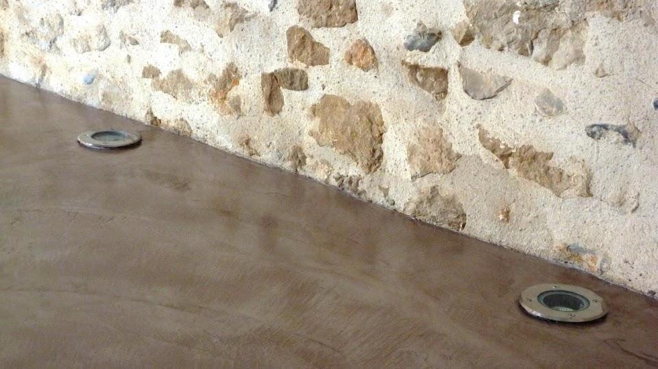 Mariage entre un sol en béton ciré et un mur en pierre