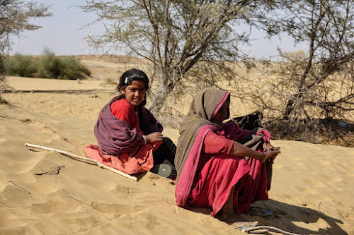 India. Rajasthan Thar Desert Camel Trek. An old lady and her grand-daughter stopping by.