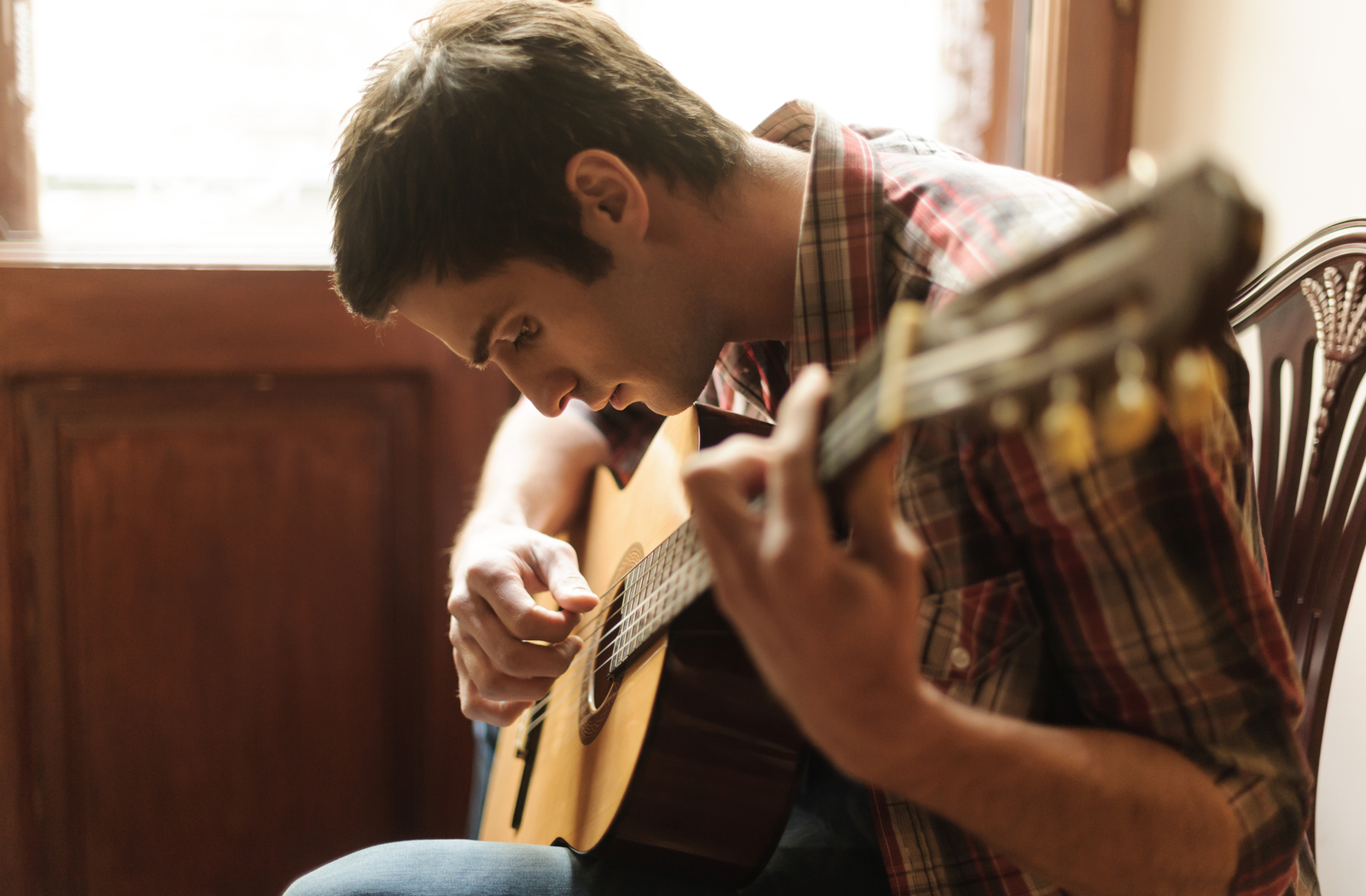 Man playing a guitar, a new hobby to help him stay sober