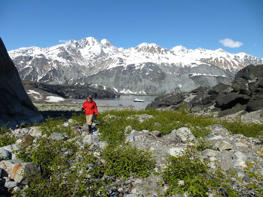 A hiker explores the pristine wilderness of Glacier Bay in Alaska with Safari Explorer in the background.