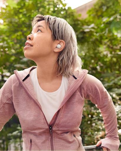 Una mujer toma aire y se relaja después de hacer mucho ejercicio. Sus Pixel Buds A-Series no se han movido de su sitio.