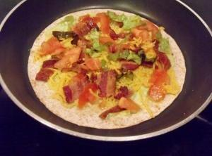 Heat Tortilla in the skillet just until warm. Add cheese, bacon, tomato and lettuce.