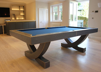 the arc pool table on wooden flooring in front of a home bar