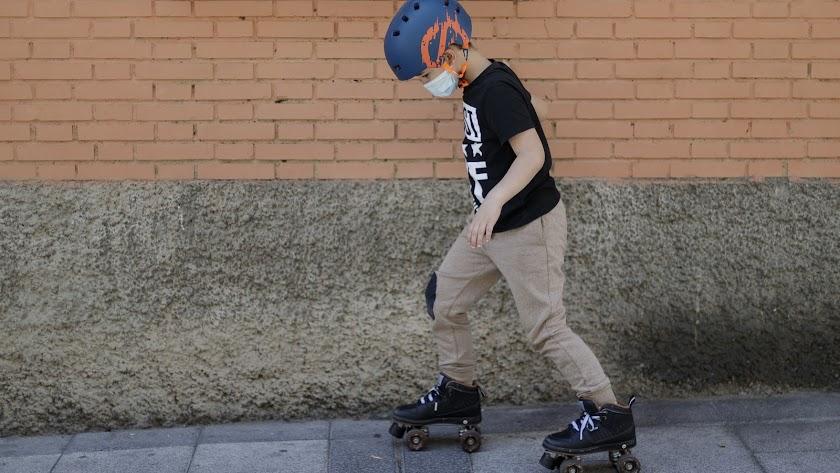 Un niño con mascarilla patina por una calle durante la Fase 2.