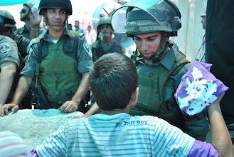 Photo: A young boy waves an Olive Revolution scarf at an Israeli soldier during the demonstration.