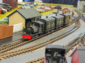 Photo: 006 An interesting train formed from a set of lined black liveried Glyn Valley coaches hauled by a nicely made Peco James 0-4-0ST arrives at the terminus station .