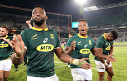 Springbok captain Siya Kolisi (L), Sbusiso Nkosi (C) and Aphiwe Dyantyi (R) celebrate victory over England to seal the three-match Test series 2-0 in a match between South Africa and England at the Free State Stadium, Bloemfontein on June 16 2018.