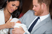 Prince Harry, Duke of Sussex and Meghan, Duchess of Sussex, pose with their newborn son Archie Harrison Mountbatten-Windsor in St George's Hall at Windsor Castle on Wednesday.