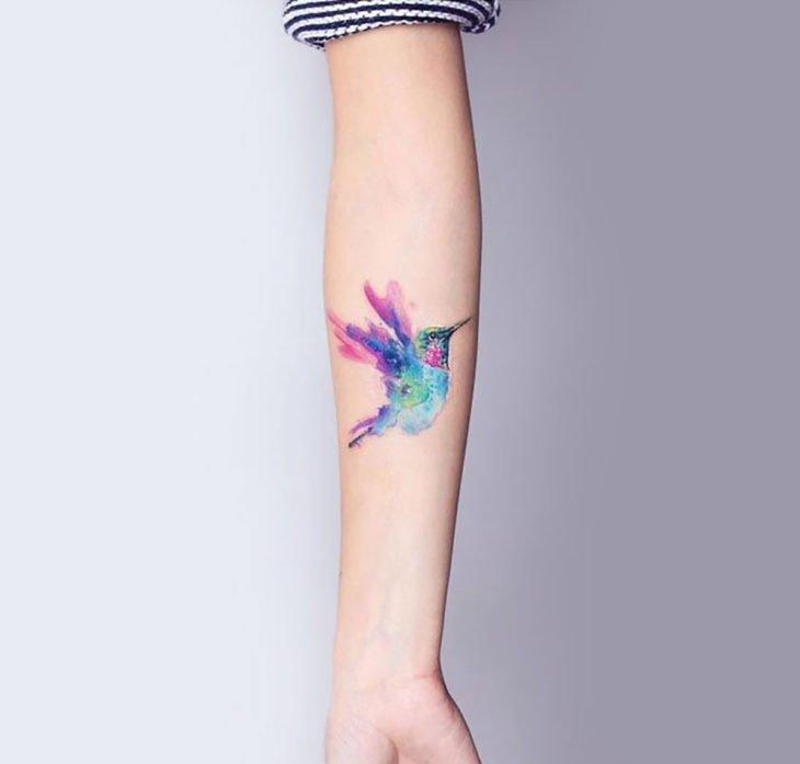 Tatuagem de beija-flor em aquarela nos braços de uma mulher