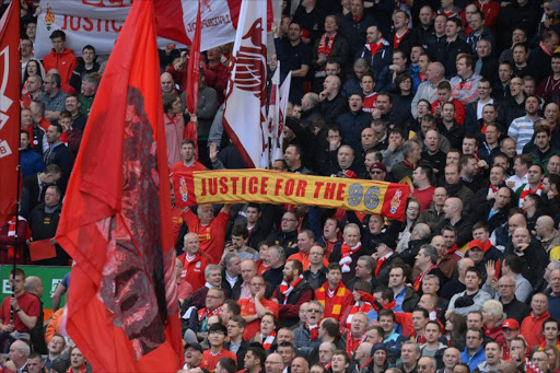 Fans in the Kop of Anfield stadium in Liverpool, England, wave banners in memory of victims of the 1989 Hillsborough disaster before a football match between Liverpool and Manchester City in April 2014.