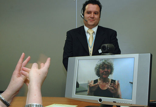 Interpreter stands by computer to translate speech to sign language