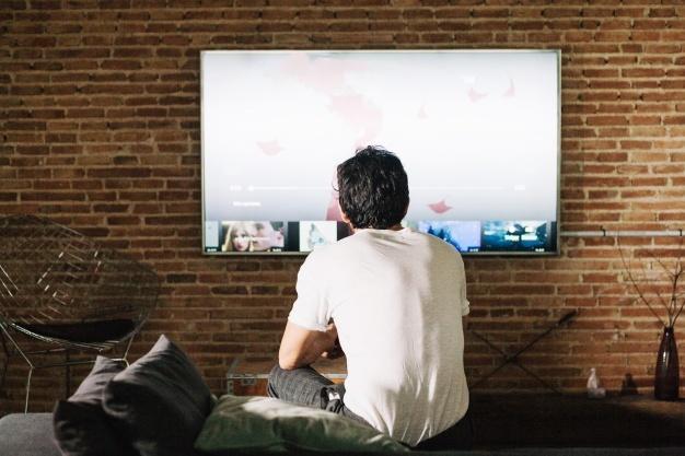 Cara de costas assistindo televisão