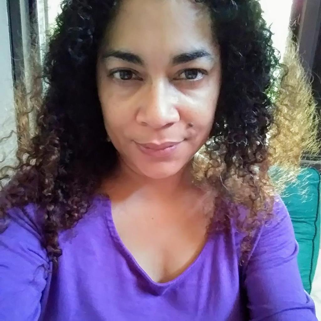 Selfie of a woman with curly hair smiling and wearing a deep purple scoop neck long sleeve shirt