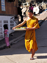 Photo: monk carrying tray of food for merit-making ceremony