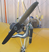 Photo: The Bloop engine is a 25 horsepower Vittorazi Moster 185 (185 cubic centimeters displacement) with its 1.3 meter (diameter) carbon composite propeller, a modern paramotor system. The translucent plastic fuel tank will hold 2-1/2 gallons of aviation gasoline mixed with synthetic oil. The combination air filter and inlet silencer is the big light brown bulb mounted on the carburetor. The red spot on the carburetor is where I attached the magneto groundng wire onto an engine bracket and taped it over. The prop tends to get oily because it passes through the exhaust stream, which still has a lot of oil in it that was mixed into the fuel. The utility bag mounted on the back of the seat is useful for stowing small tools, lubricant, hats, cameras, and so forth. One spark plug, one cylinder, one carburetor, and a pull rope for starting. The butterfly carburetor includes a fuel pump so the gas tank can be located below the engine. There is no float bowl, the fuel system is sealed except for the static port on the fuel tank.