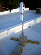 "Photo: 4foot antenna mast fashioned from a Dish-TV J-mount and 1/2"" electrical conduit, weighted down with cinderblocks."