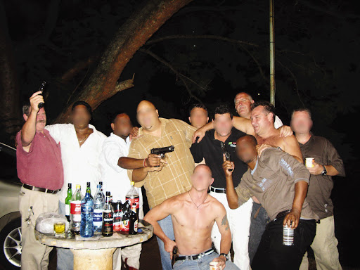 Members of the Cato Manor organised crime unit celebrate just hours after killing five robbery suspects on the N3 highway near Camperdown on January 21 2009. The members with visible faces (not blurred) are, from left, Captain Eugene van Tonder, Captain Mossie Mostert and Captain Anton Lokum