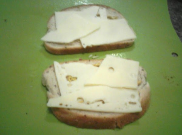 Flip bread slices over,spread with mustard, and put a slice of swiss cheese on...