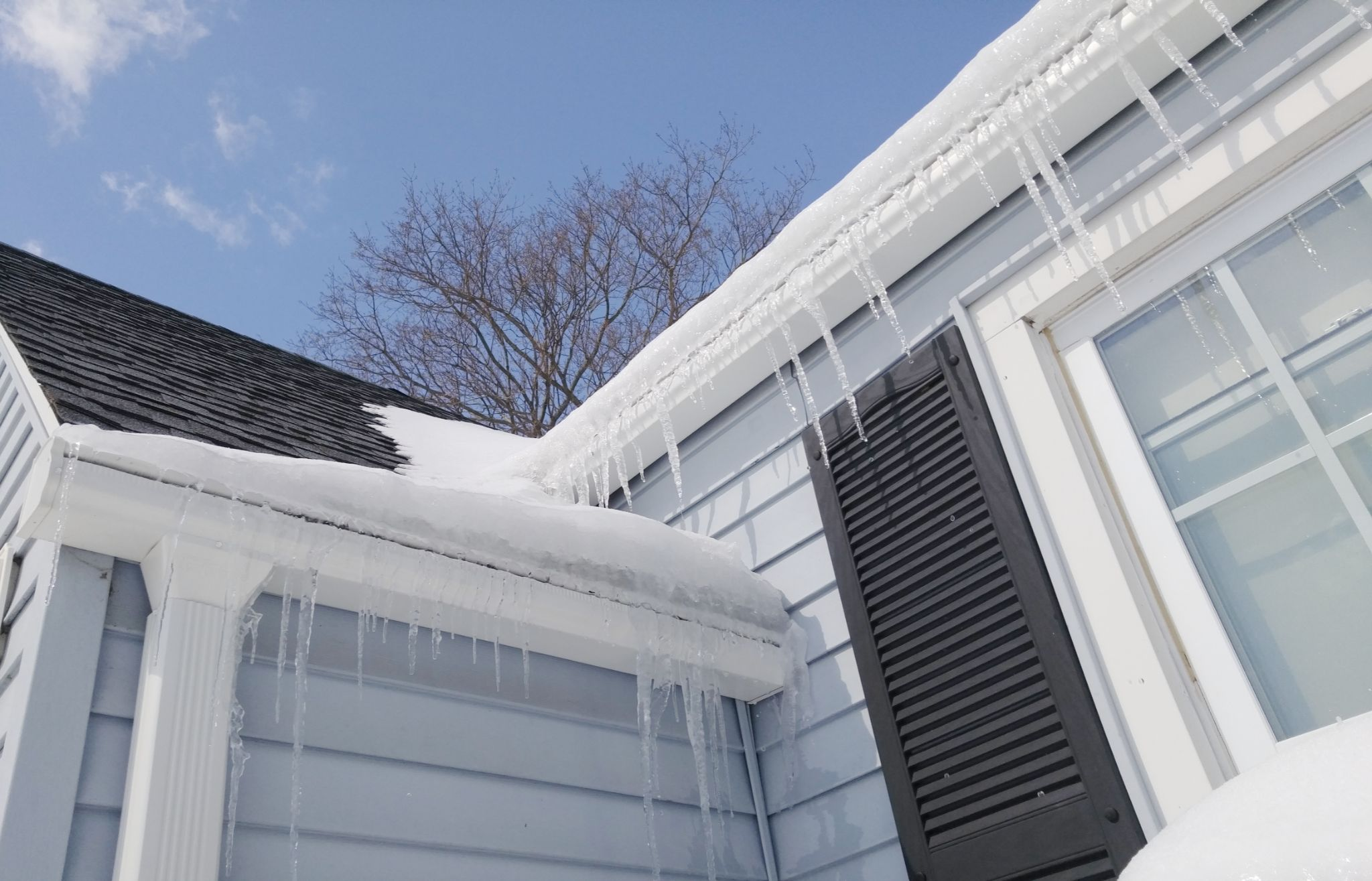 Icicles hanging from a roof and gutters.