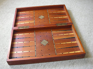 Photo: CH305 Interior with backgammon board.  The playing surface is aligned at right-angles to that of the exterior chess-board (as it has to be to work sensibly for backgammon - creating a natural 'bar'), and all the holes are correctly lined up on the points. As more than 4 pieces can rest on any point, the holes continue into the central section. I have not seen a set with pegged draughts/backgammon counters to see if they could be stacked in some way.